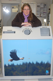 Toni Falk, Land Use Clerk Technician is pictured with one of the multibin recycling bins that features her photo.