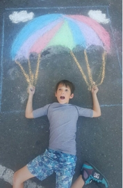 Picture of a boy playing with a chalk art umbrella.
